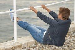 Mitte alterte die kaukasische Frau, die auf dem Seestrand sitzt Stockfotografie