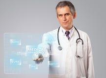 Mitte alterte Doktor, der moderne medizinische Art des Knopfes bedrängt Lizenzfreie Stockfotos