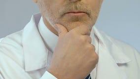 Mitte alterte Doktor, der Problem löst und Entscheidung mit der Hand auf seinem Kinn trifft stock video