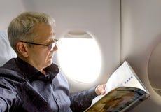 Mitte alterte kaukasische Mannlesezeitschrift in den Flugzeugen Lizenzfreie Stockfotos
