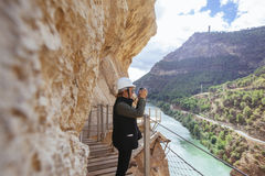 Mitte alterte und abenteuerliche Frau mit dem Sturzhelm, der Fotos auf einer Klippe macht Lizenzfreies Stockbild