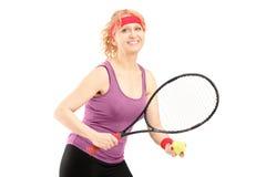 Mitte alterte weiblichen haltenen Tennisschläger und -ball Lizenzfreie Stockfotos