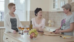 Mitte drei alterte die reifen Frauen, die die Stellung nahe moderner Tabelle zu Hause plaudernd mitten in Küche in Verbindung ste stock video