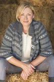 Mitte gealterte blonde Frau, die auf Hay Bale sitzt Stockbilder