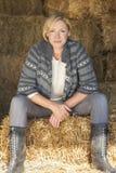 Mitte gealterte blonde Frau, die auf Hay Bale sitzt Stockfotos