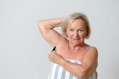 Mitte gealterte blonde Frau, die ihre Achselhöhle rasiert Stockfotos