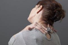 Mitte gealterte Dame, die Selbstmassage tut Lizenzfreie Stockfotografie