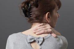 Mitte gealterte Dame mit Rückseite oder Nackenschmerzen lizenzfreie stockfotografie