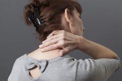 Mitte gealterte Dame mit Rückseite oder Nackenschmerzen stockbild