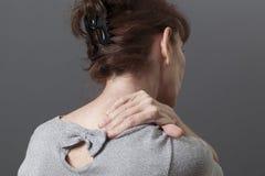 Mitte gealterte Dame mit Rückseite oder Nackenschmerzen stockfotografie