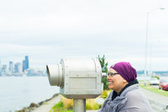 Mitte gealterte Frau, die allgemeines Teleskop verwendet Stockbild