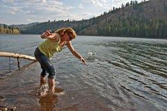 Mitte gealterte Frauen-überspringende Felsen im See Stockbild