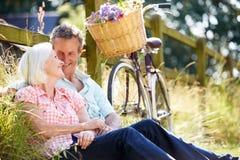 Mitte gealterte Paare, die auf Land-Zyklus-Fahrt sich entspannen stockbild