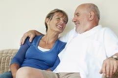 Mitte gealterte Paare, die auf Weidencouch sitzen Lizenzfreie Stockbilder