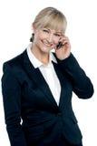 Mitte gealterte Unternehmensfrau, die auf Mobile spricht Stockbilder