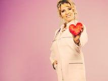 Mitte gealterter blonder Doktor genießen ihre Arbeit Stockbild