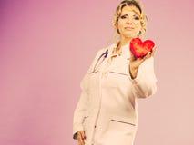 Mitte gealterter blonder Doktor genießen ihre Arbeit Lizenzfreie Stockbilder
