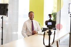 Mitte gealterter Geschäftsmann, der ein Unternehmensvideo herstellt stockfotografie