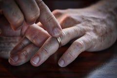 Mitte gealterter Mann, der seinen Heiratsring off nimmt Stockfotografie
