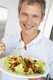 Mitte gealtertes Fleisch fressendes ein gesunder Salat lizenzfreies stockfoto