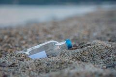 Mitteilung in der Flasche fest im Sand Stockbild