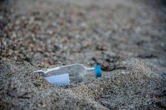 Mitteilung in der Flasche fest im Sand Stockfotografie