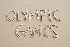 Mitteilung der Olympischen Spiele handgeschrieben im Sand Lizenzfreie Stockfotografie
