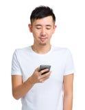 Mitteilung des jungen Mannes Kontrollam Handy Lizenzfreie Stockbilder