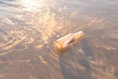 Mitteilung in einer Flasche auf Strand verwischte Gegenstand mit abtract Licht f Lizenzfreie Stockfotos