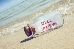 Mitteilung in einer Flasche, die noch auf sandigem Strand hofft Lizenzfreie Stockfotos