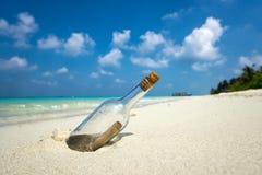 Mitteilung in einer Flasche wusch sich an Land auf tropischem Strand Stockbild