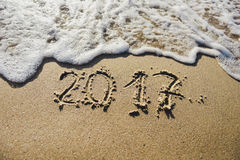 2017, Mitteilung geschrieben in den Sand am Strandhintergrund Lizenzfreie Stockbilder