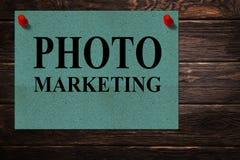 Mitteilungen 'FOTO-MARKETING 'geschrieben auf Grünbuchstände als Anzeige auf einer Holzoberfläche stockbilder