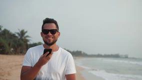 MITTEILUNGS-Spracherkennungsanwendung ai hübschen jungen touristischen Manngebrauchstelefon Smartphone Audiowährend des Sonnenunt stock video