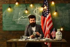 Mitteilungsblatt und Darlehen Mitteilungsblattkonzept mit dem bärtigen Mann, der Dollargeld an USA-Flagge hält lizenzfreie stockfotos