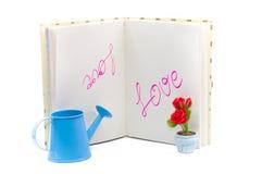Mitteilungsliebe buchstabierte im Tagebuchbuch mit Rotrose und Bewässerungsca Lizenzfreie Stockbilder