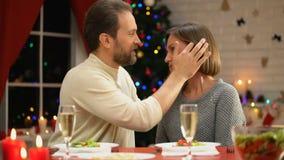 Mittel-gealterter Mann, der zart Frau auf Weihnachtsabend, liebende Beziehungen in der Familie küsst stock video