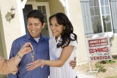 Mittel-Handing Over House-Schlüssel zu den Paaren Stockfotografie