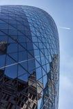 MITTEL-LONDON/ENGLAND - 18 05 2014 - Wolkenkratzerreflexionen werden in den Fenstern der Essiggurke gesehen, während ein Flugzeug Lizenzfreie Stockbilder