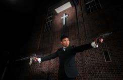 Mittel-Mörder, der Gewehre in Richtung zum Ziel zeigt Stockbild