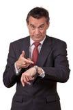 Mittelalter-Geschäftsmann, der auf Uhr zeigt stockbild