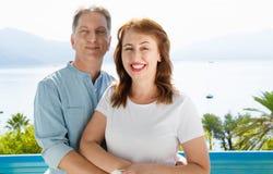 Mittelalterfamilienpaare nehmen im Urlaub auf Seehintergrund Zuflucht Sommerleutereise zum tropischen Strand Sommerzeitfreizeit lizenzfreie stockbilder