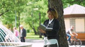 Mittelalterfrau, die Anmerkungen in einem Tagebuch im Park macht stock footage