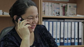 Mittelalterfrau, die am Handy im Büro spricht Porträt der lächelnden Frau stock video