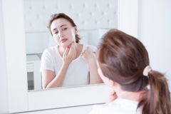 Mittelalterfrau, die im Spiegel auf Gesicht schaut Falten und Antialternhautpflegekonzept Selektiver Fokus stockfotografie