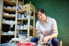 Mittelalterfrau, die Lehmgegenstand macht Der Bildhauer während der Arbeit in der Tonwarenwerkstatt lizenzfreies stockbild