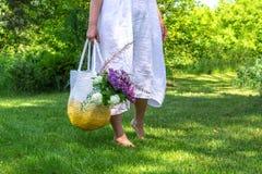 Mittelalterfrau im weißen einfachen Leinenkleid bleibt barfuß auf dem Gras im schönen Garten und hält gestrickte weiß-gelbe Tasch stockbilder