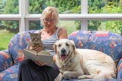 Mittelalterfrau liest ein Buch mit Haustieren zusammen Lizenzfreies Stockfoto