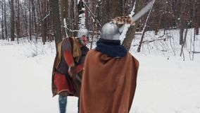 Mittelalterliche irische und frankish Krieger in der Rüstung kämpfend in einem Winterwald mit Klingen und Schildern stock footage