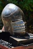 Mittelalterlicher bascinet Helm mit liftable Gesichtsmaske auf dem Scharnier gesetzt auf weaponsmith Arbeitstabelle Lizenzfreie Stockfotos